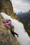 A female rock climber ascends the Takakkaw Falls route (5.6) in Yoho National Stock Photos