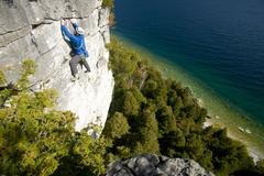 A rock climber on a high traverse at White Bluffs, Bruce Peninsula, Ontario, Stock Photos