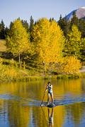 A young asian woman uses her paddle board on a small lake in Canmore, AB Stock Photos