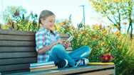 Happy child girl using smartphone and laughing sitting on the bench in the park Stock Footage