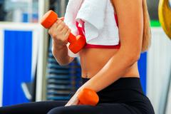 Body part sport girl lift dumbbells in gym. Biceps foreground. Stock Photos