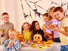 Halloween party with children eating trick or treat. Stock Photos