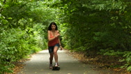 Young  teenager   girl    with  skateboard in green park. Slow motion Stock Footage