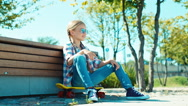 Happy girl in sunglasses sitting on the skateboard near bench in the park Stock Footage