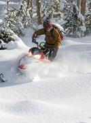 A solo snowmobiler makes his way down unchartered powder in the Monashee Stock Photos