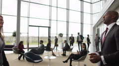 4K Business man & woman greet in busy meeting area of large modern office Stock Footage