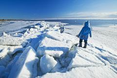A man with looks out over washed up ice piles, along Lake Winnipeg, Manitoba, Stock Photos