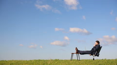 Businessman working on laptop in the field. Thinks about the project. Stock Footage