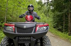 A single male ATV quad rider makes his way down the trail near Powell river on Stock Photos