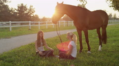 SLOW MOTION: Two girls sitting on the grass and hanging out with brown horse Stock Footage