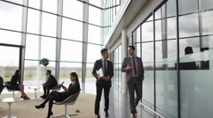 4K Businessmen talking as they walk through lobby of corporate office building Stock Footage