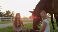 SLOW MOTION: Two girls sitting on the grass and hanging out with horse at sunset Stock Footage