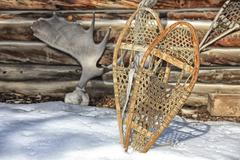 A pair of snowshoes with moose antlers in the background beside an old cabin, Stock Photos