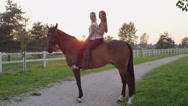 SLOW MOTION: Two cheerful girls riding bareback beautiful brown horse at sunrise Stock Footage