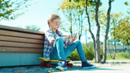 Happy girl 7-8 years in sunglasses playing in game on her smartphone sitting Stock Footage