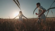 Happy, young couple running across the wheat field,sunset light, summer season Stock Footage
