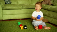Baby boy is playing, sitting at the home Stock Footage