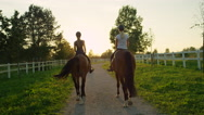 SLOW MOTION: Two girlfriends horseback riding brown horses into the sunset Stock Footage