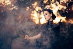Evil Queen Holding Scepter in Misty Forest Stock Photos