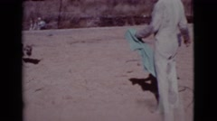 1968: a man with a blue towel outside playing with a dog COTTONWOOD, ARIZONA Stock Footage