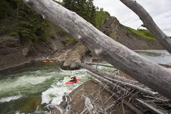 A male kayaker surfs some rapids on the Highwood River, Alberta, Canada Stock Photos