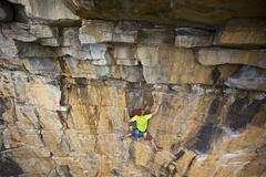 A young man rockclimbing through a tough roof at Lost Boys crag in Jasper Stock Photos
