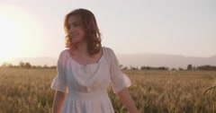 Beautiful girl running on sunlit wheat field. Slow motion 240 fps. Sun lens Stock Footage