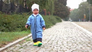 Unhappy baby boy is walking on road, slow motion Stock Footage