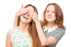 Girl covering eyes with hands to her friend portrait on white background Stock Photos