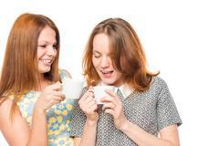 Girlfriends enjoying a delicious tea, portrait on a white background Stock Photos