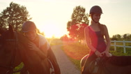 SLOW MOTION: Two cheerful young girls enjoying horse ride at magical sunset Stock Footage