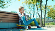 Happy girl in sunglasses sitting on the skateboard near bench in the park and Stock Footage