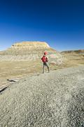 A hiker looks out over the Killdeer Badlands, East Block, Grasslands National Stock Photos