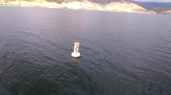 Aerial shot of buoy floating on lake shore water Stock Footage