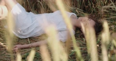 Beautiful model girl lies and dreams in a field of wheat,slow motion Stock Footage