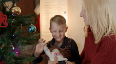 Son playing with hand made doll under christmas tree Stock Footage