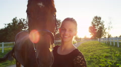 CLOSE UP: Portrait of strong brown horse and pretty happy girl on sunny day Stock Footage