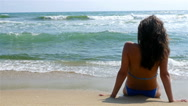 Woman relaxing on the beach, looking at sea water, waves splashing in her body Stock Footage