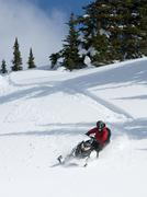 A very steep slope makes it difficult for a snowmobiler to descend in the Stock Photos