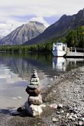 An inukshuk sits on the shoreline while tour boat DeSmet is docked on Lake Stock Photos