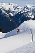 A backcountry snowboarder sprays a powder turn while on a cat ski trip. Stock Photos