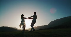Romantic young couple silhouette. woman and man holding hand in circle together Stock Footage
