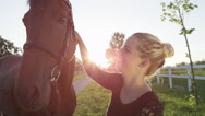 CLOSE UP: Portrait of brown horse and cheerful girl petting and kissing him Stock Footage