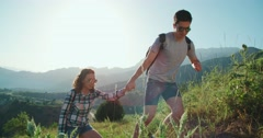 Couple climbing mountain range, hand reaches out to help,slow motion Stock Footage