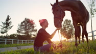 SLOW MOTION: Beautiful smiling girl sitting on meadow and feeding her horse Stock Footage