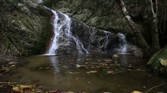 Nature waterfall in the mountain rock inside the forest with pond Stock Footage