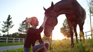 SLOW MOTION: Beautiful cheerful girl sitting on grass, scratching, petting horse Stock Footage