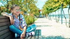 Cute schoolgirl 7-8 years in sunglasses sitting on the bench and waving hand Stock Footage