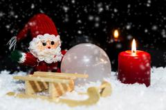 Santa claus, a sledge and a candle in the snow, black background with snowfal Stock Photos