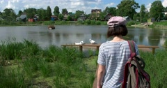 The girl walks to the pond, three white goose Stock Footage